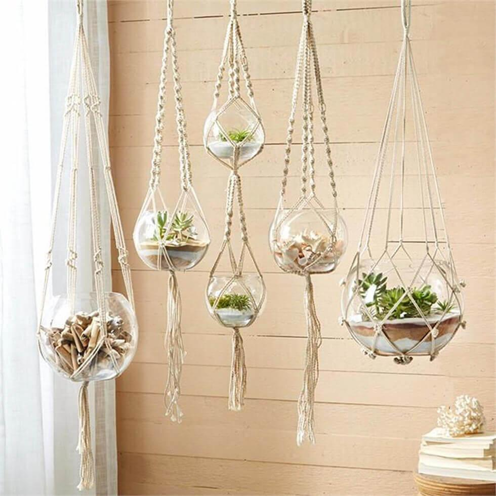 Glass planters suspended from macrame hangings.
