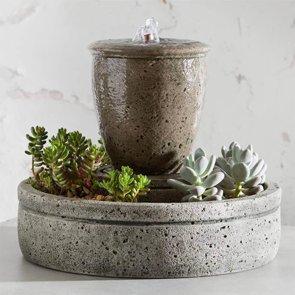 Cement indoor water feature surrounded by plants.