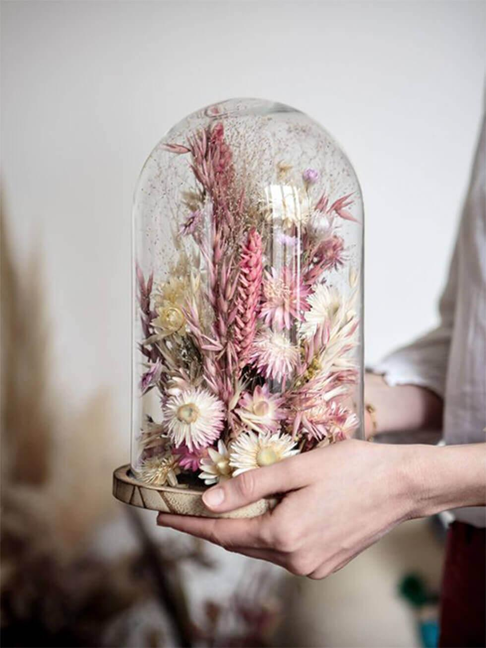 Dried flowers arranged in a sealed bell jar for decoration.