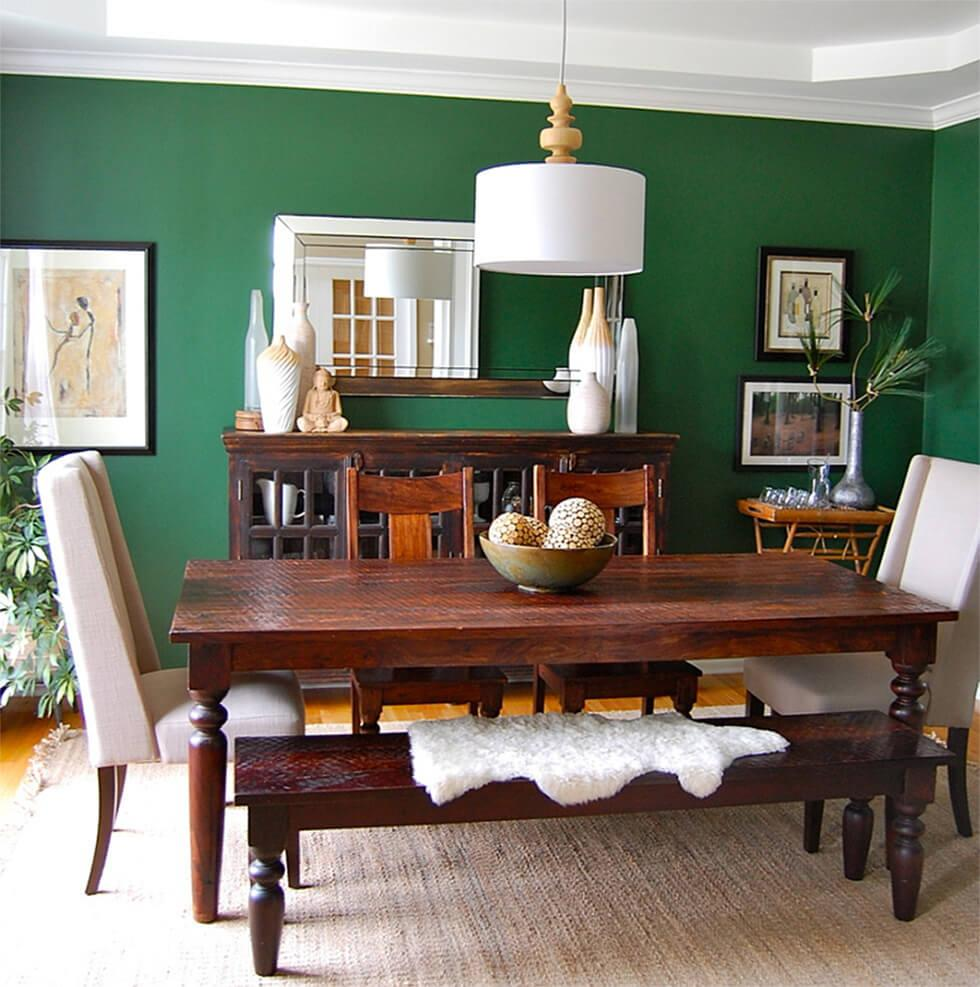 dark wood dining table in a forest green dining room