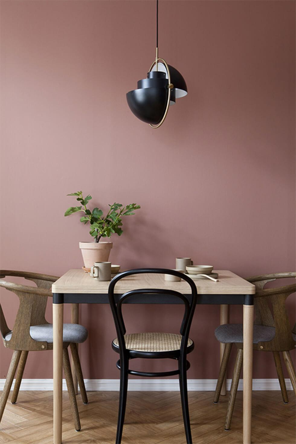 two tone light wood and black dining set in a mauve nordic dining room