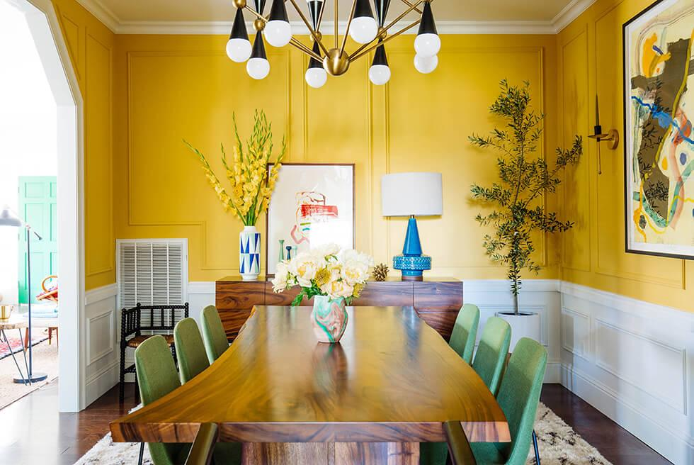 mustard yellow half wall in a modern artsy dining room