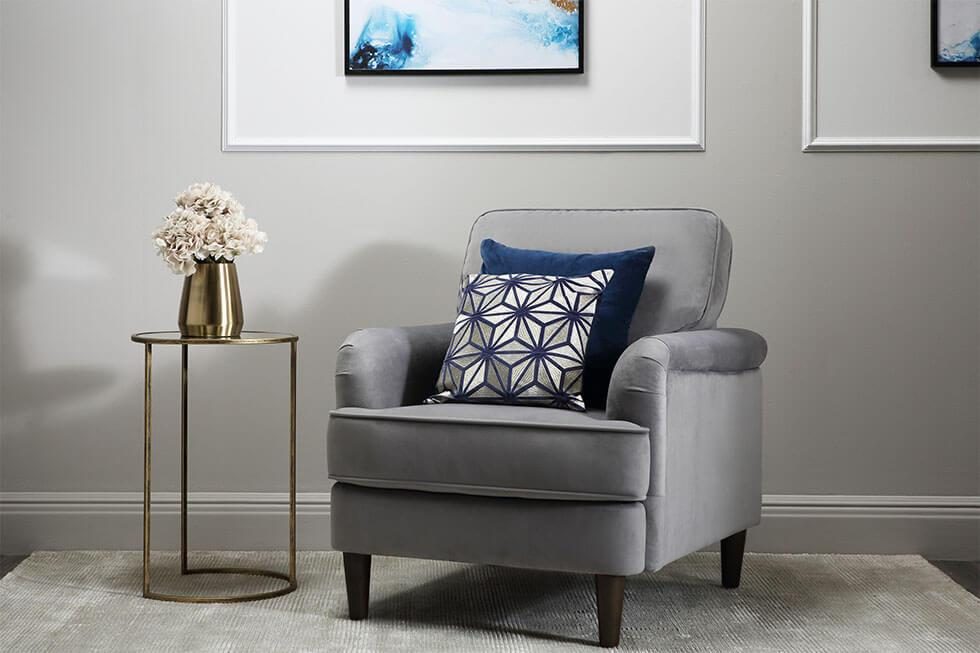 Grey armchair beside a gold side table with thin legs.