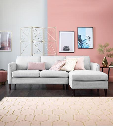 Light grey sofa in a light pink room.