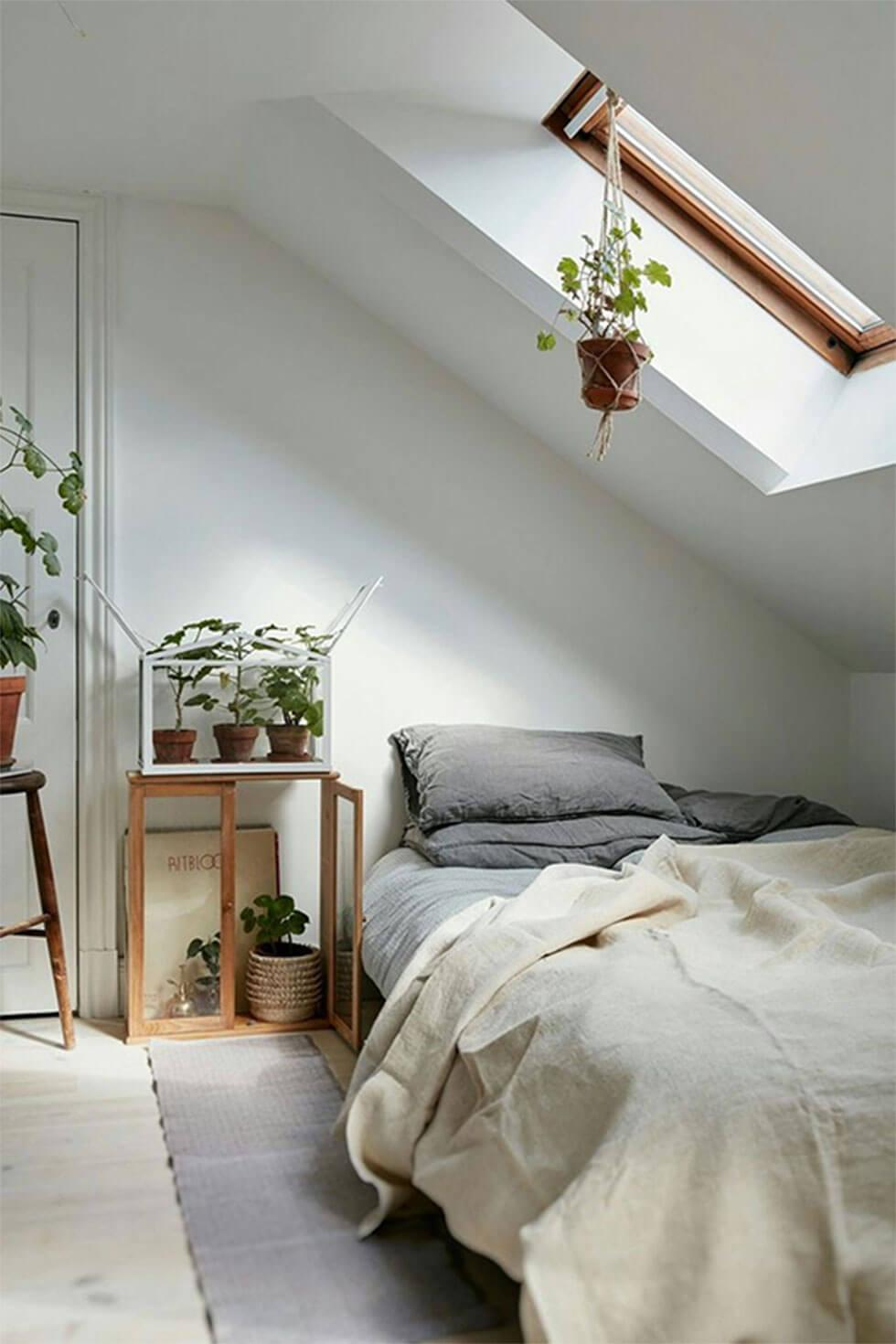 Neutral loft bedroom with grey pillows, white bedding and greenery