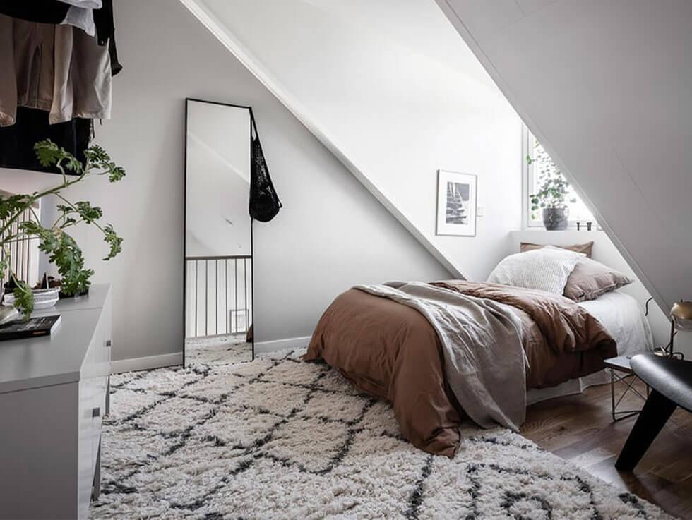 Cosy Scandinavian loft bedroom in a neutral palette