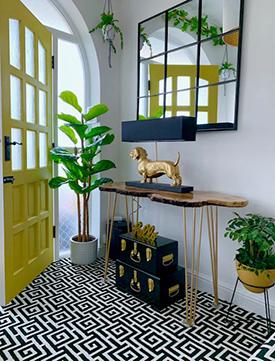 Yellow door and metallic light in a neutral tone entryway