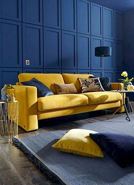 Mustard yellow sofa paired with pantone classic blue walls in a modern living room