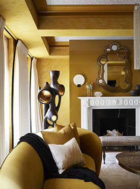 Yellow walls and furnishings in a traditional living room with fireplace