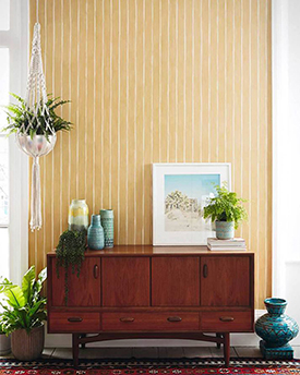 Yellow and white striped wallpaper and a dark wood console table