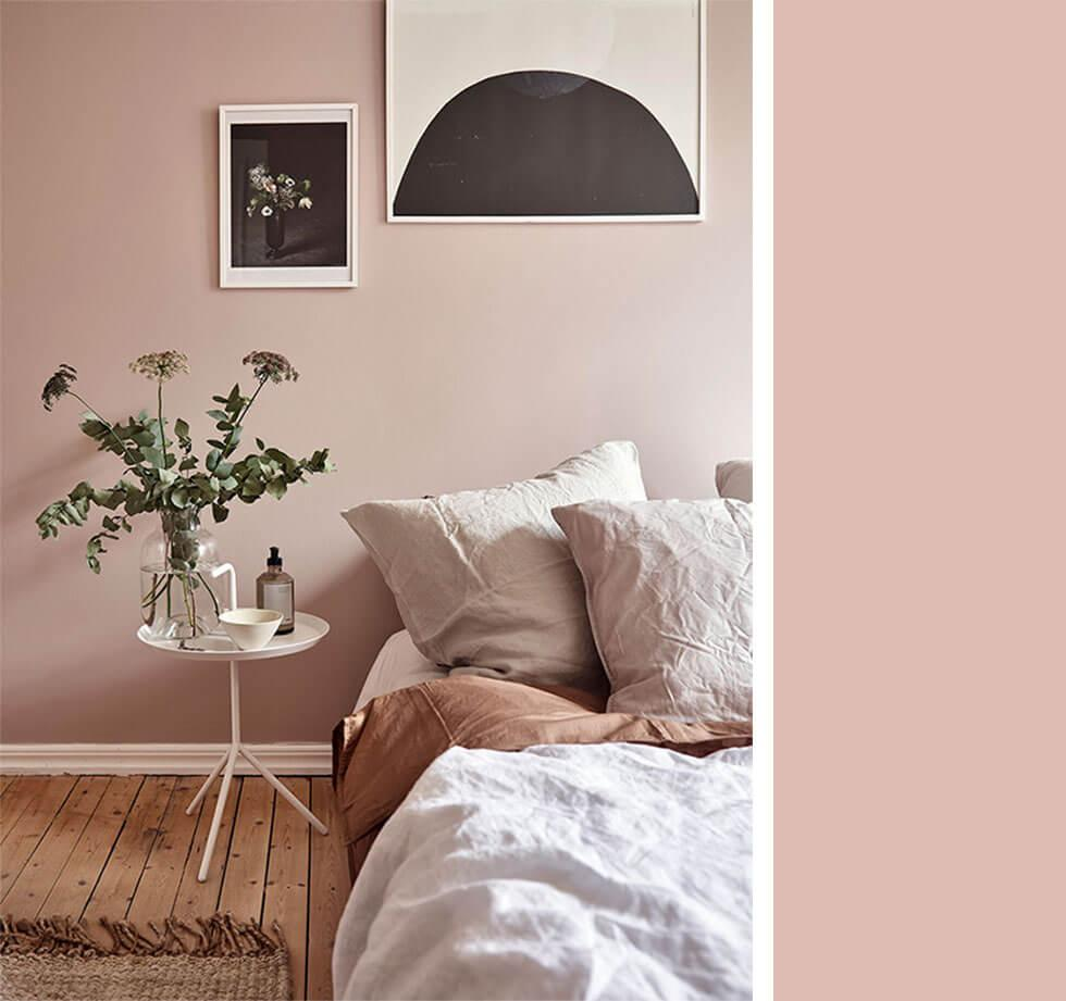 Dusky pink bedroom with bedding, bedside table and artwork