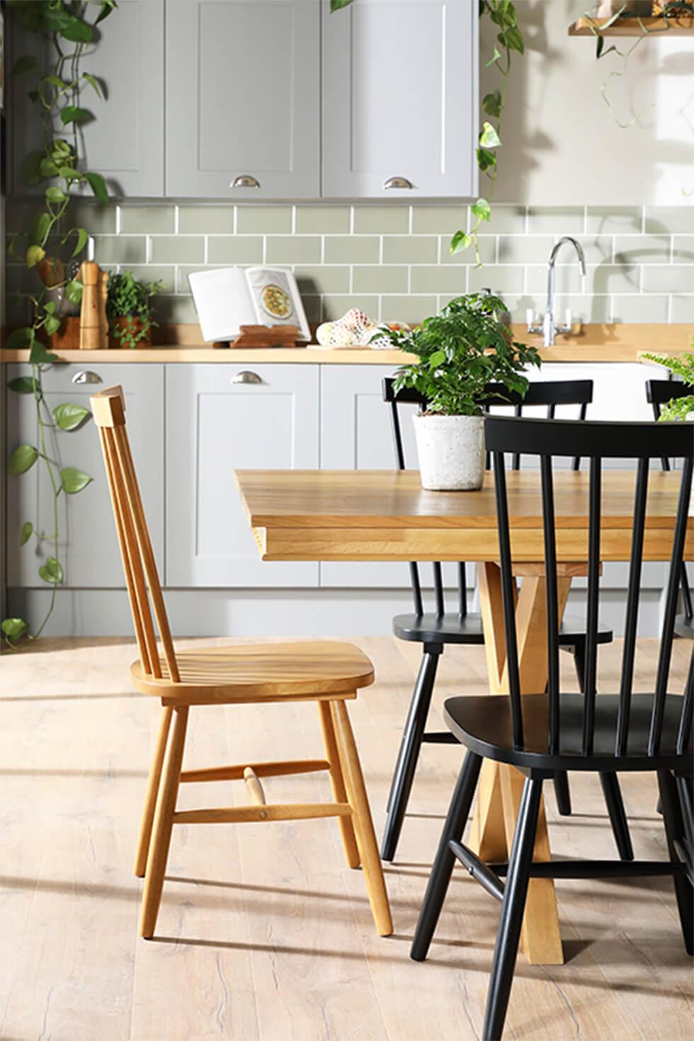 Mismatched chairs and an oak dining table in a contemporary kitchen with plants
