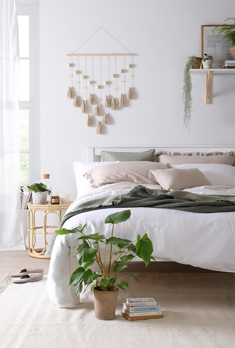 A white wooden bed in a calm and soothing neutral bedroom