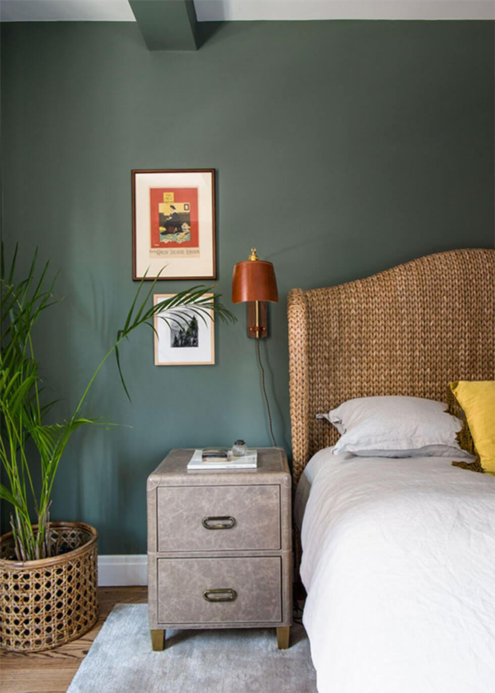 A bedroom wall painted in green, with natural materials around the room.