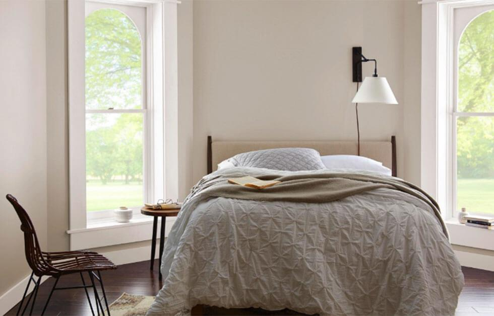A bedroom with off-white painted walls and soft neutral tones.