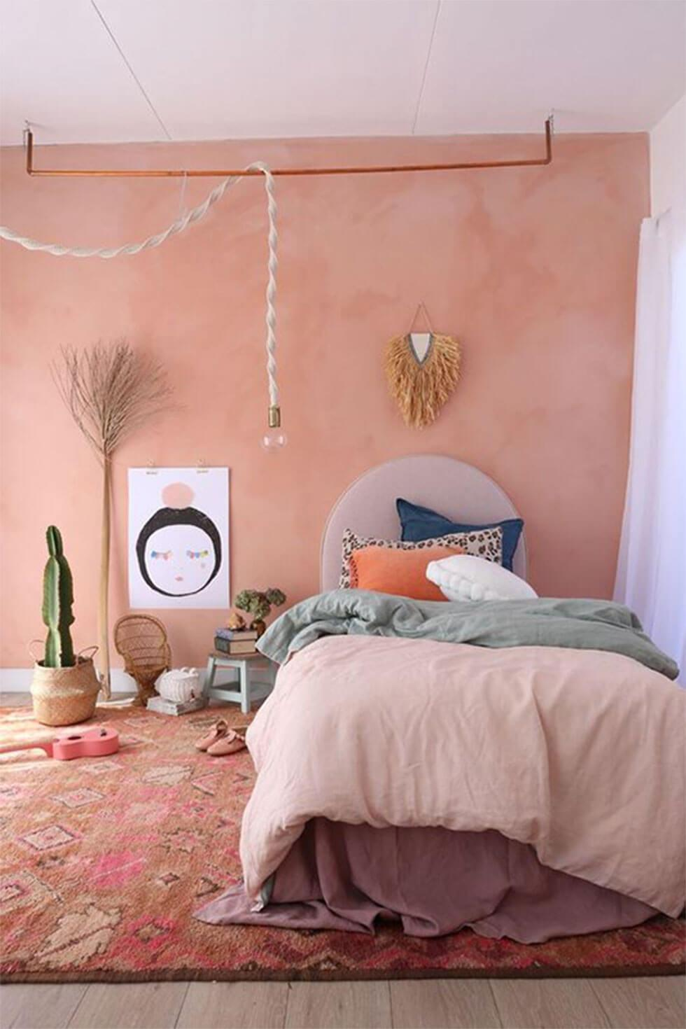 Bedroom walls painted dusky pink with bronze accents for a bohemian glam look.