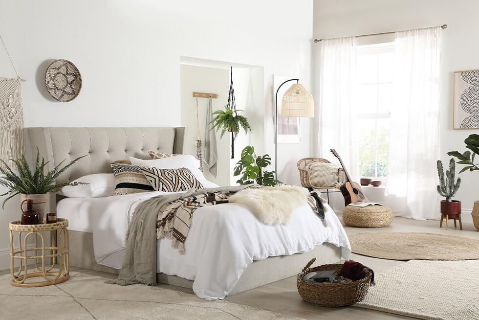 Oatmeal fabric bed in a comfortable neutral modern boho bedroom