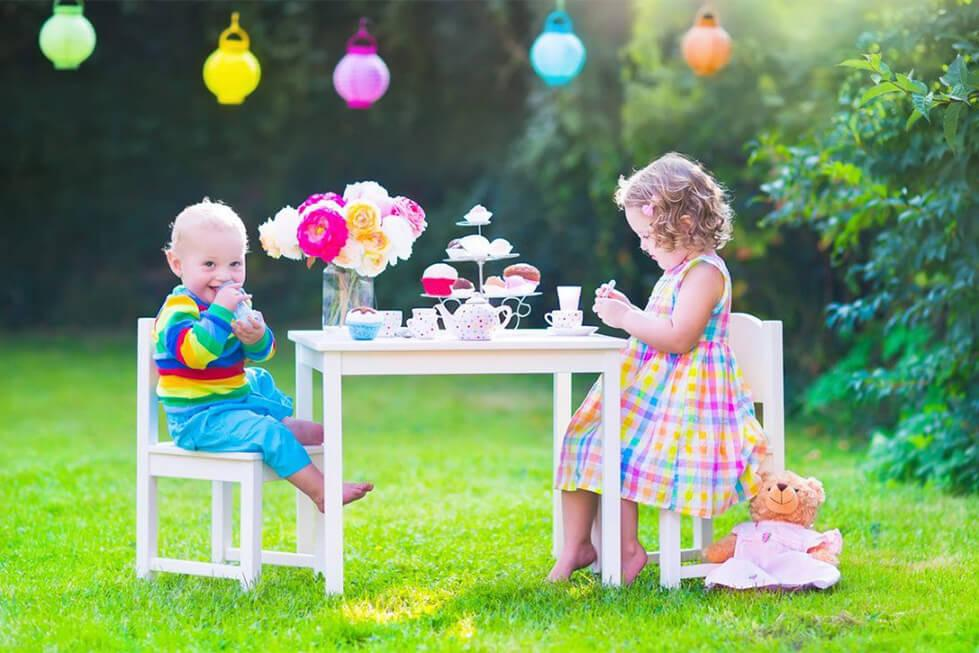 Toddlers having a tea party with soft toys
