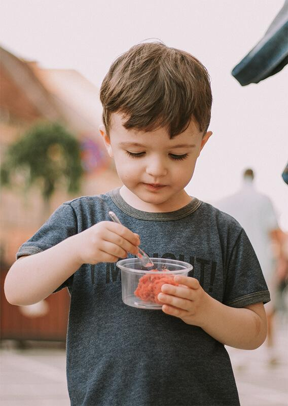 young boy eating with a spoon