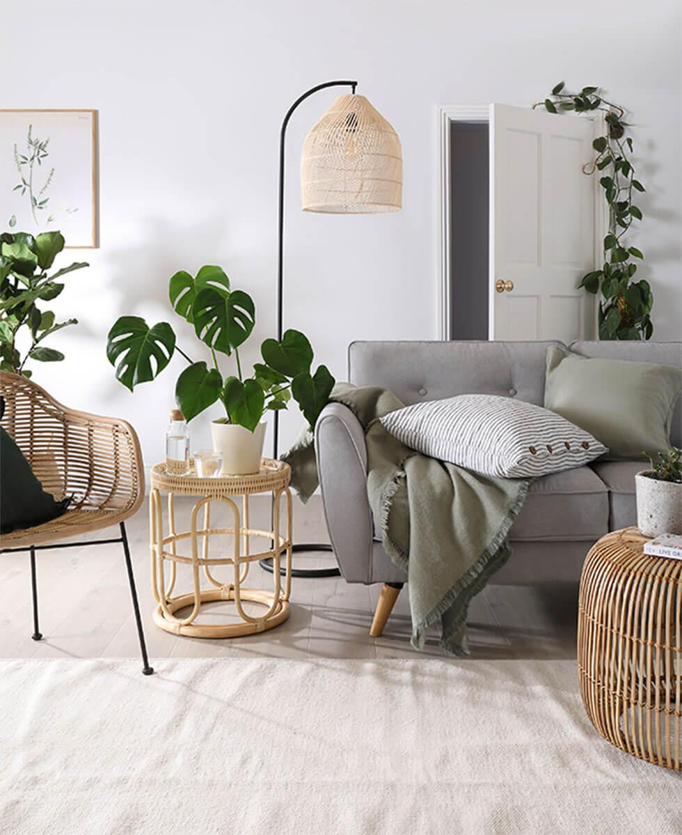 Modern bohemian living room with grey sofa, rattan accessories and indoor plants