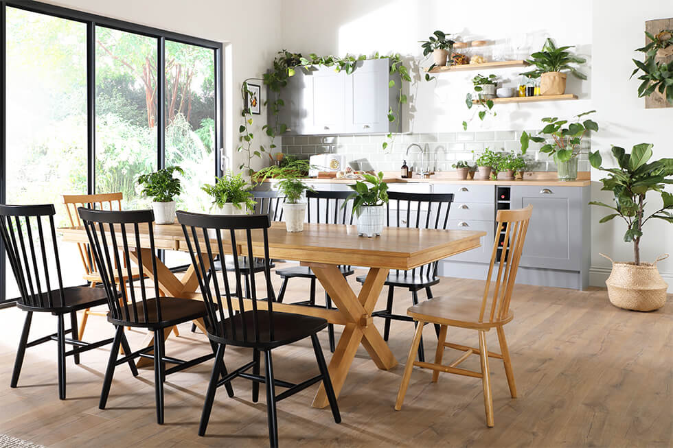 Large wooden dining table with mismatched black and wooden chairs with lots of plants