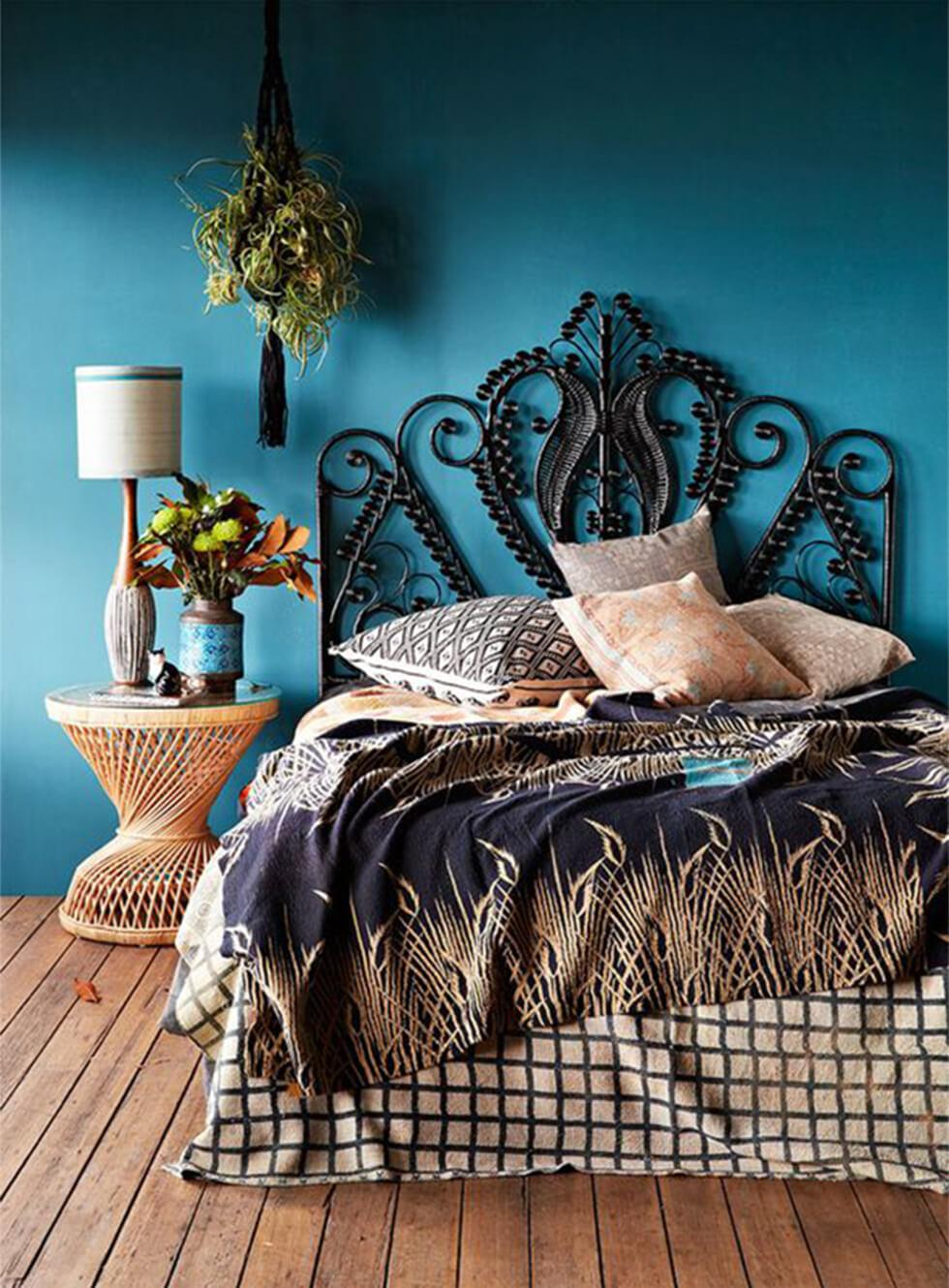 Teal bedroom with a rattan side table and ornate peacock rattan bed