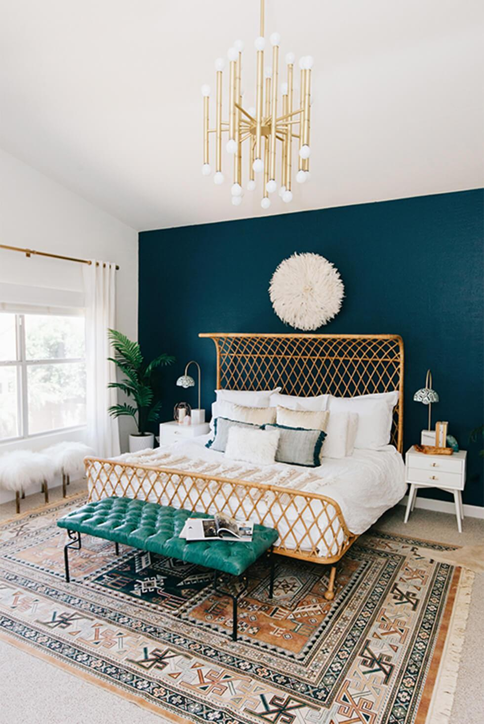 Tropical teal bedroom with a large rug, gold chandelier and statement rattan bed