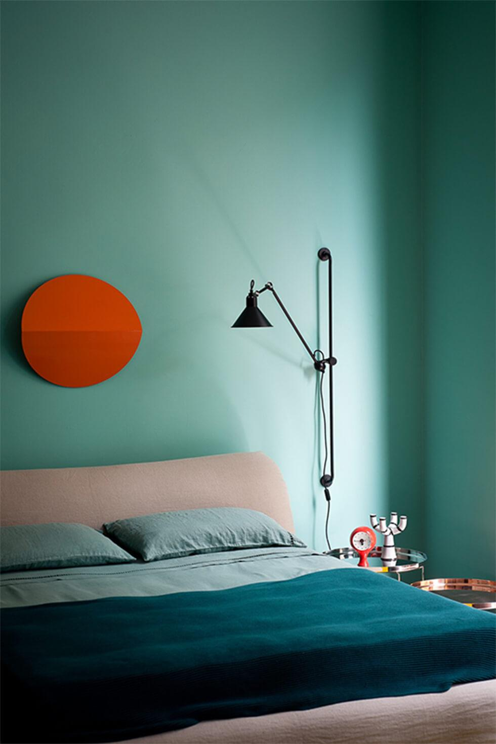 Teal bedroom with contrasting circular orange wall art and teal bedding