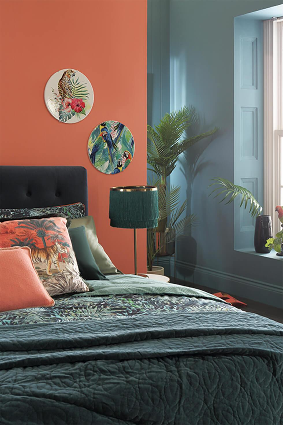 Tropical teal bedroom with contrasting orange and teal walls, and a dark velvet bed.