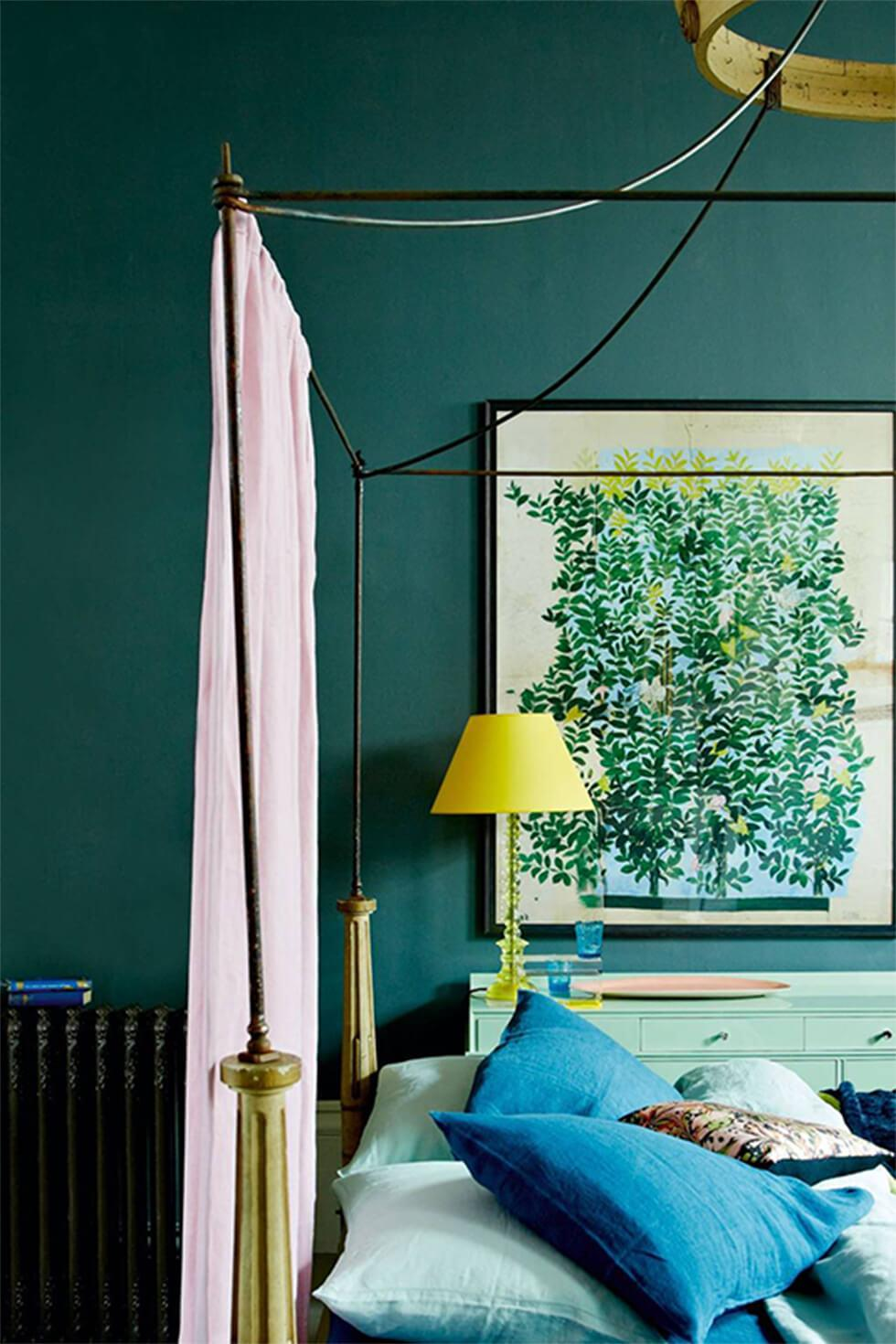 Eclectic teal bedroom with a poster bed, green art, and pink drapes.