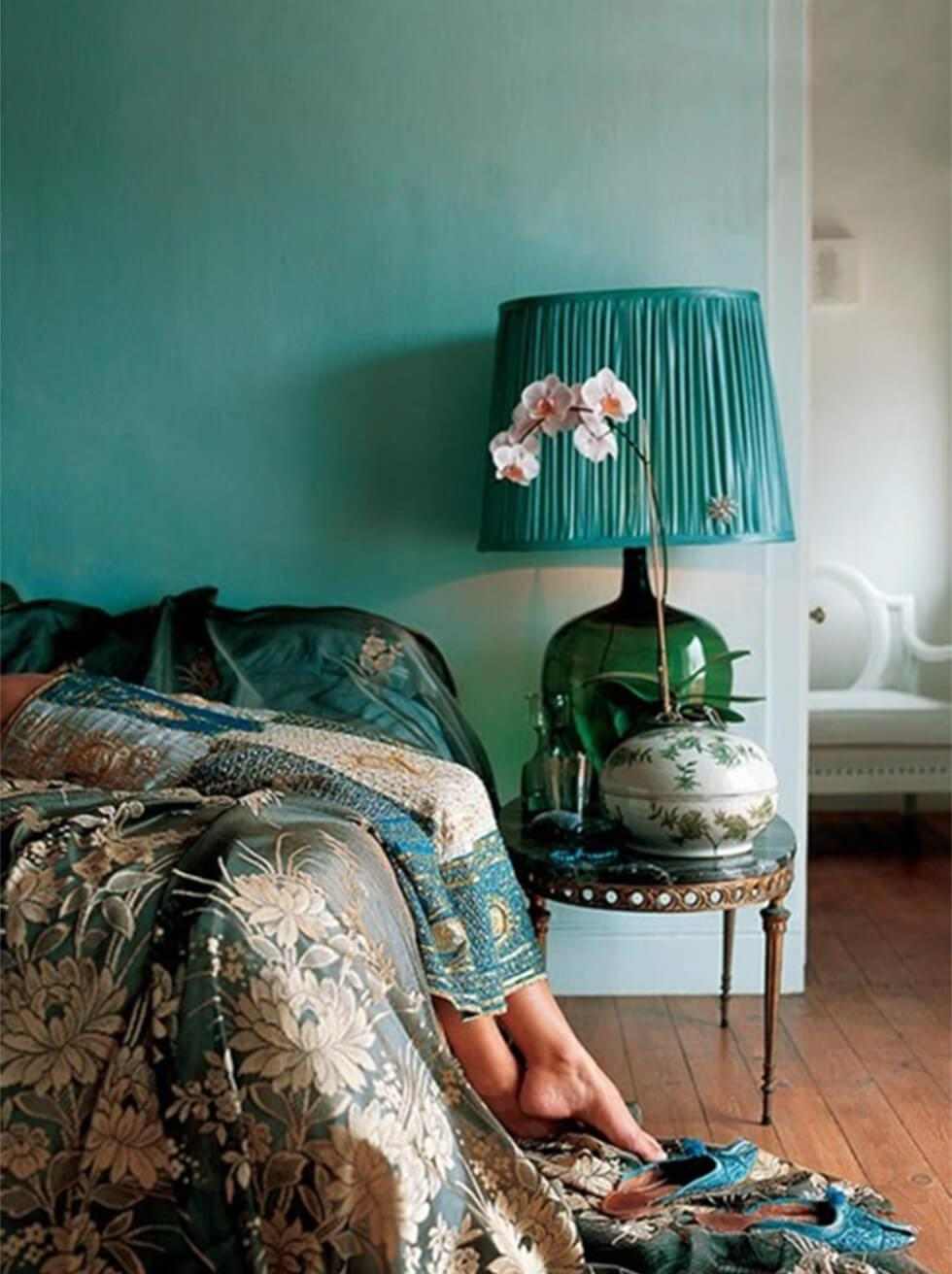 Bohemian bedroom with varying shades of teal on prints, bedding and accessories.