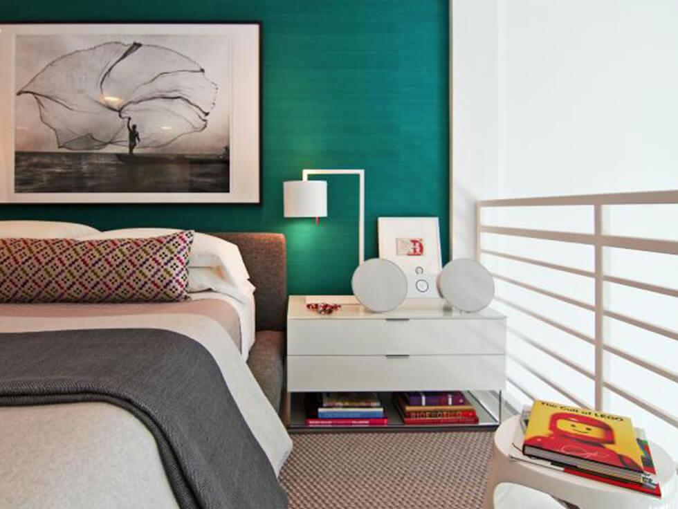 Clean modern teal bedroom with a feature wall and white, minimalist furniture.