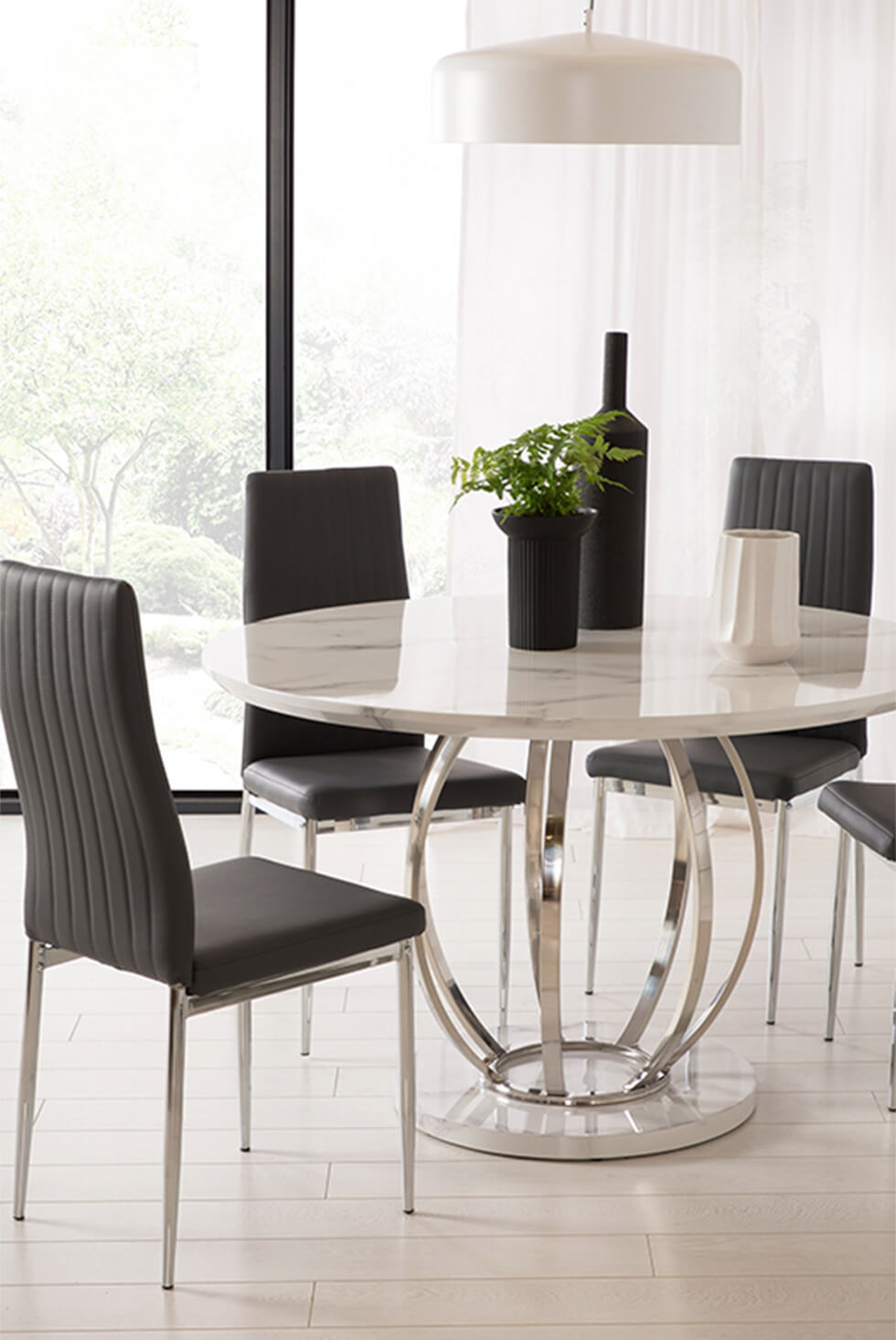 Round white marble dining table and black leather dining chairs in a modern dining room
