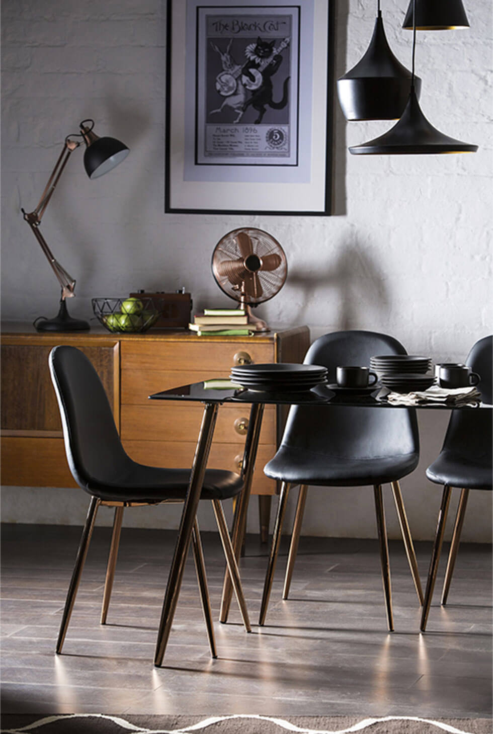 Black dining table and chairs set with copper finished legs in a modern lux setting