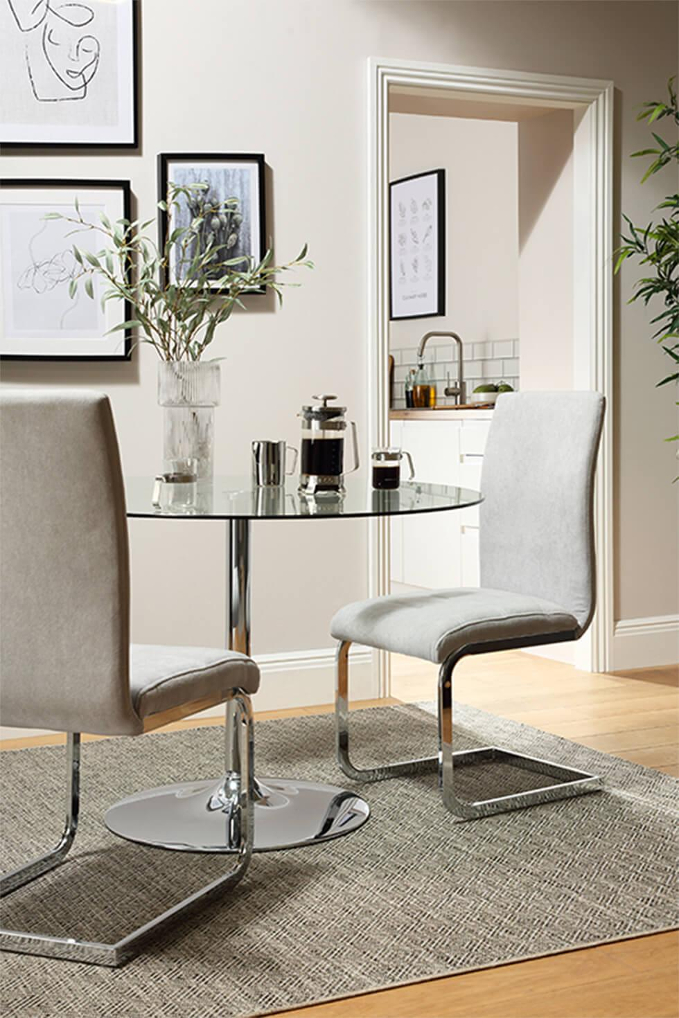 Minimalist small dining room with chrome and glass dining table and cantilever chrome dining chairs in soft grey