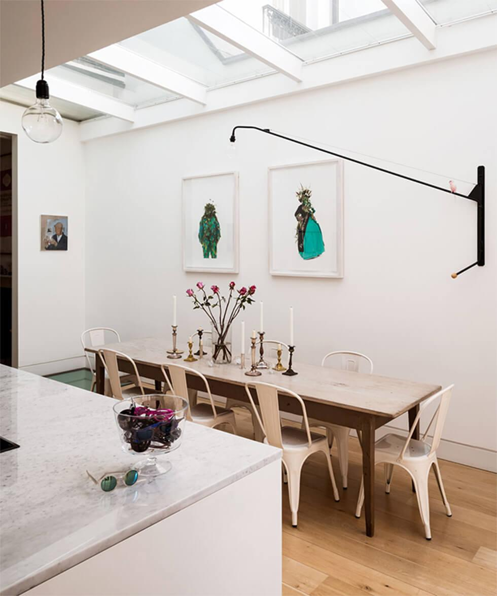 Narrow white dining room with a slim, rectangular wooden dining table, cream chairs and statement lighting