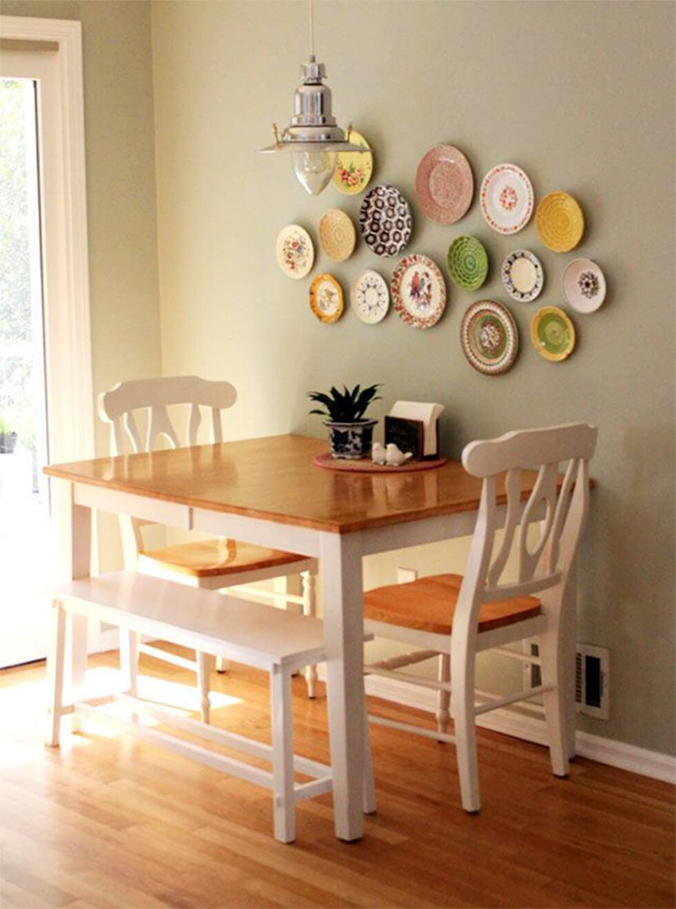 Small wooden and white dining table with matching chairs and a white wooden bench with plates on the wall as decor