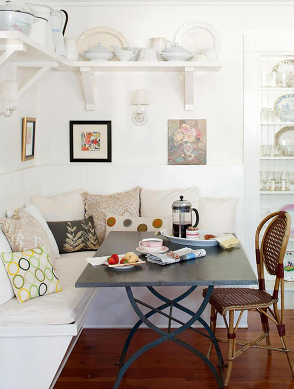 A small dining room with a cream banquette against white walls, framed artwork and a dark dining table