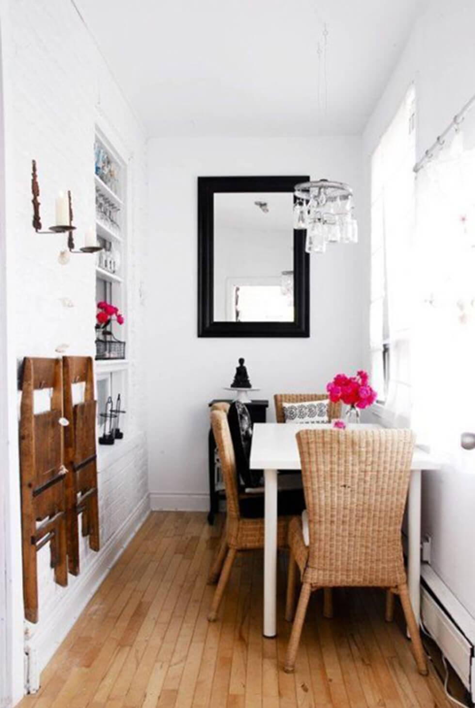 Bright and airy small dining room with white table against a wall, wicker chairs and a mirror