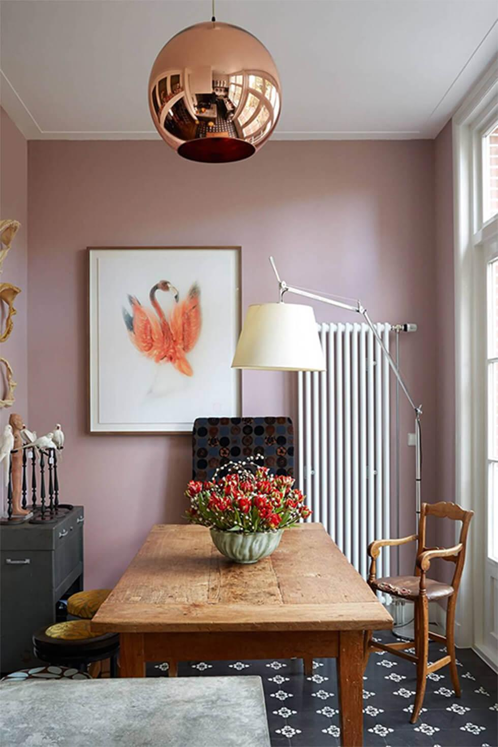 Eclectic small dining room with narrow rectangular wooden table, rose gold lamp, soft mauve walls and framed artwork