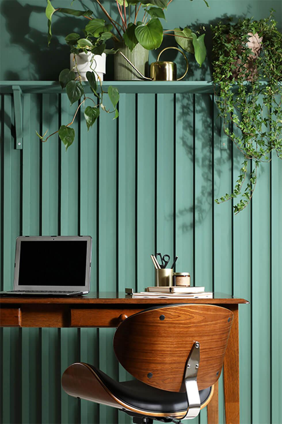 Green home office with plants and a wooden desk