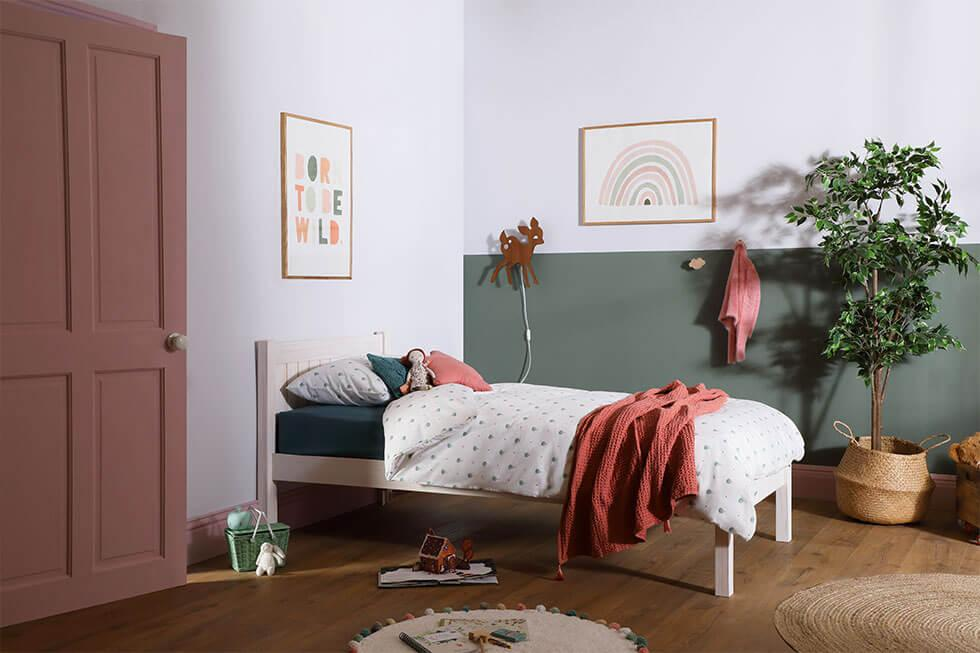 Green and pink children's bedroom with a white wooden bed