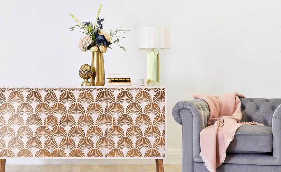 Art Deco inspired sideboard with gold detailing beside a grey velvet armchair.