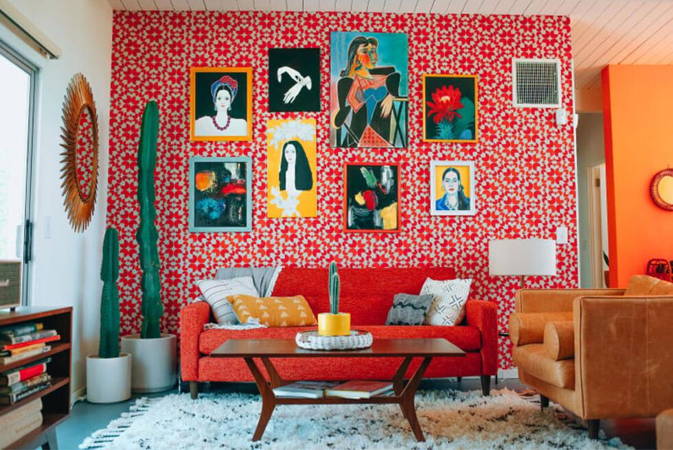 Bold and cosy small living room with high ceilings and colourful artwork hung up top.