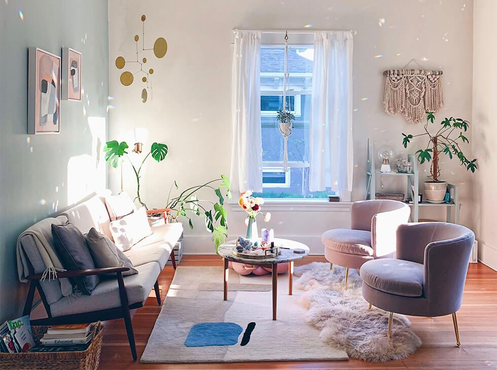 Natural daylight streaming into a cosy living room with candles and plants.
