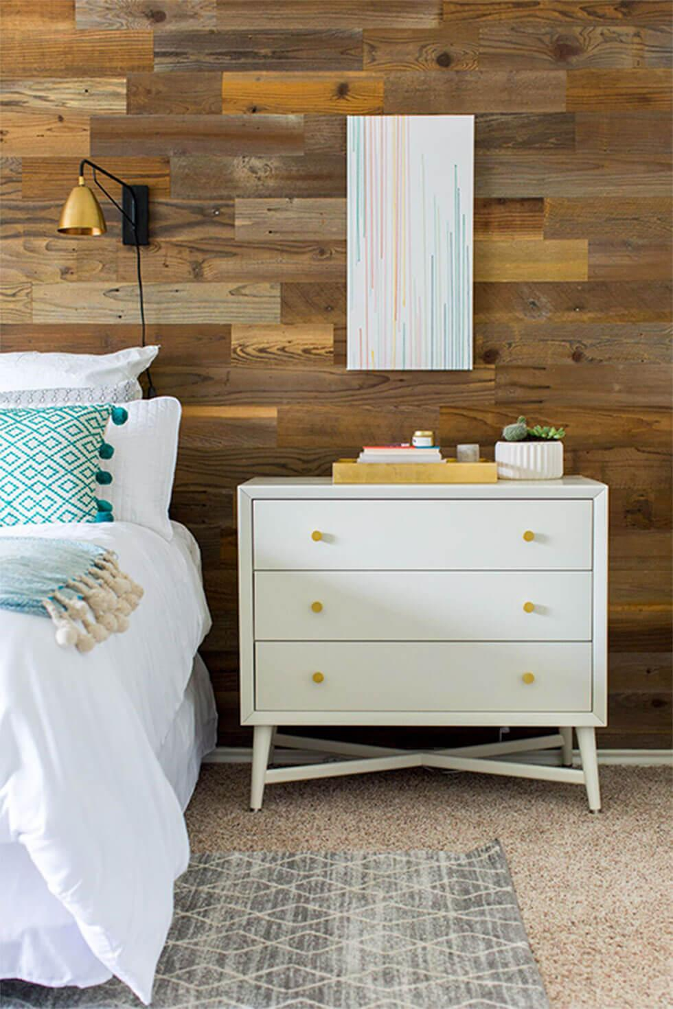 A rustic styled bedroom with a wooden feature wall.