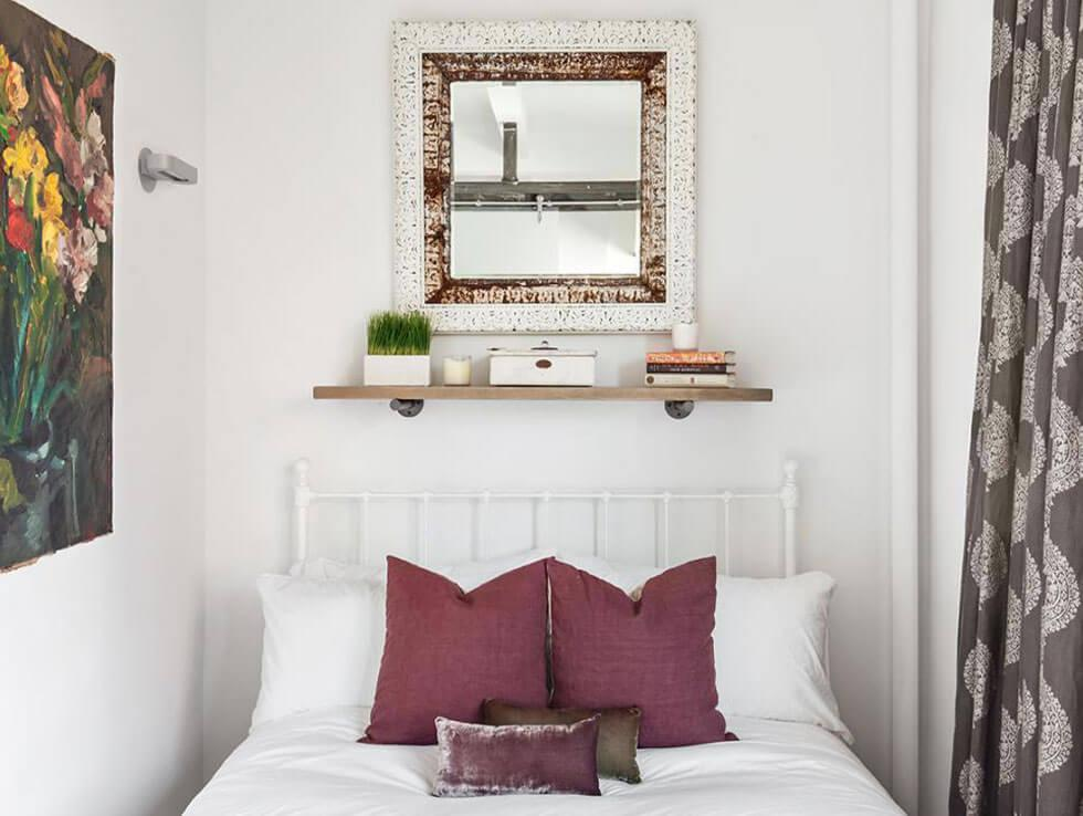A small bedroom with white walls and a mirror to maximise light.