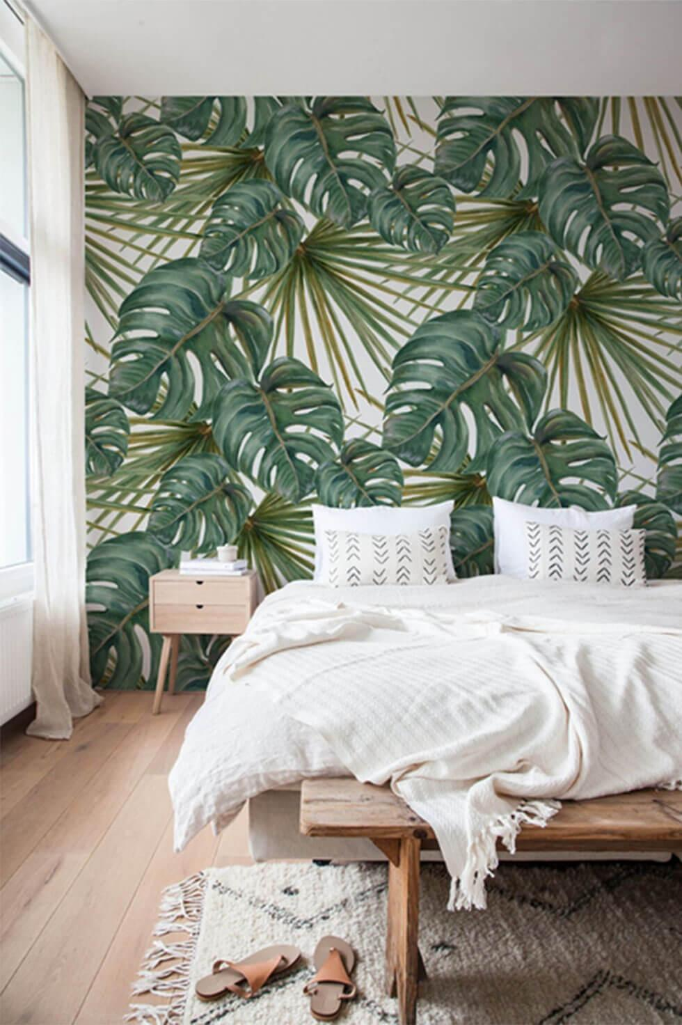 Tropical green bedroom with exotic leaf print wallpaper.
