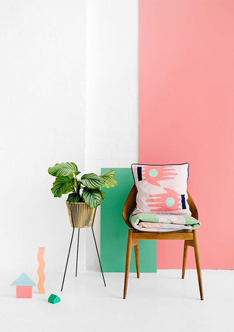 wooden chair against an energising neo-mint and coral pink wall.
