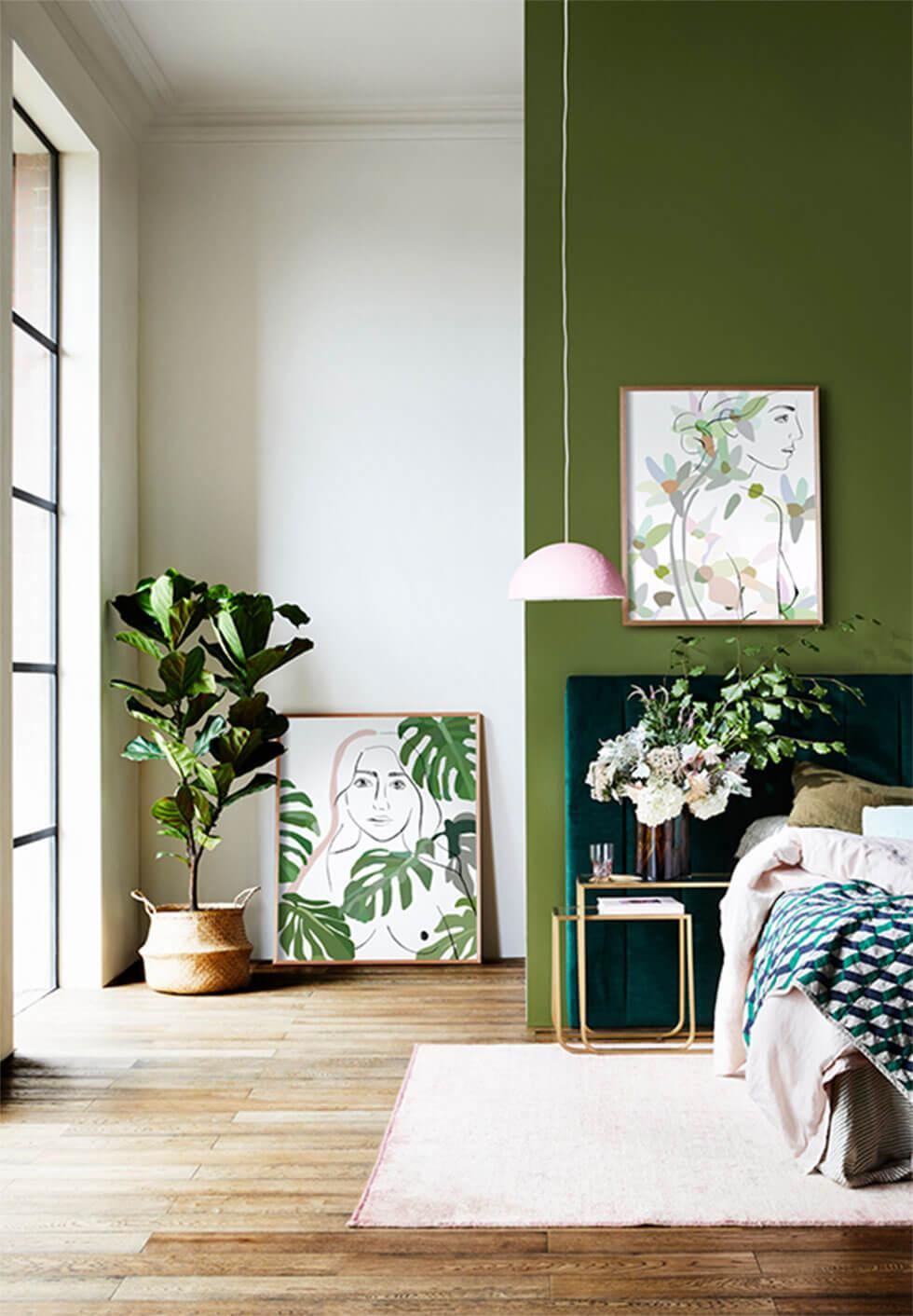 Light green bedroom with indoor plants and green artwork.